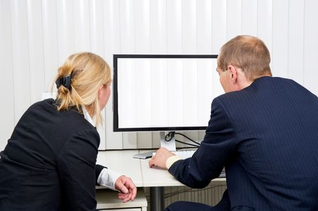 blinded: Two colleagues staring at a monitor with blinds in a blinded office