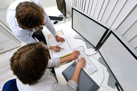 Dos ingenieros, trabajando juntos en una Oficina, uno explicando algo a otro