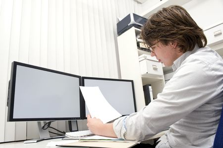 engineer computer: A designer, studying a ducument from the thick file in front of him behind his desk
