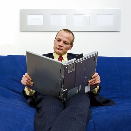 rotated: Man wearing a suit, reading an e-book, holding his laptop rotated, as if a real book
