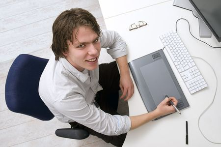Portrait of a man sitting behin a desk with keyboard, graphic tablet and monitor in an office photo