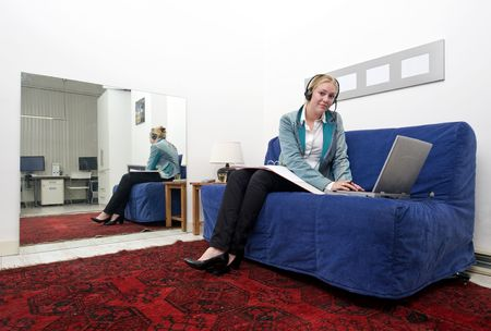 annexed: Woman working on a couch on her laptop, annexed to an office space Stock Photo