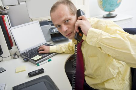 Stressful businessman making a telephone cal whilst typing on a laptop photo