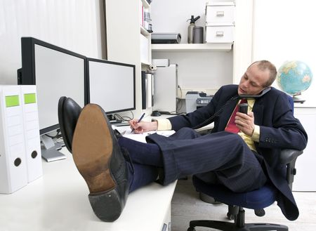 Businessman with his shoes on the desk, talking on the phone whilst making notes and holding another call photo