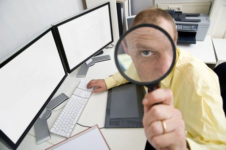watchful: The eye of a businessman, sitting behind a dual screen computer, seen through a magnifying glass, illustrating being careful, watchful and shrewd in business