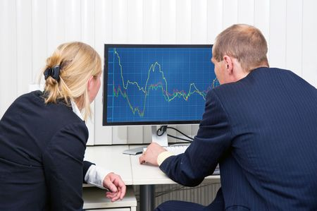 fluctuation: Two brokers analyzing (sales) trends, displayed on a flat screen monitor