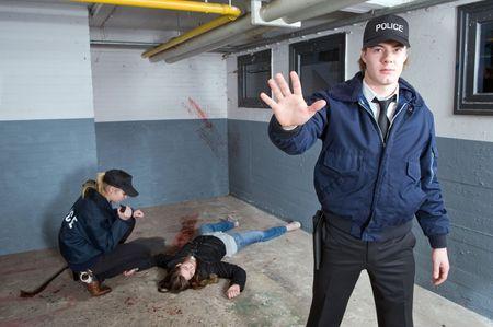 femme policier: L'officier de police gardant les spectateurs � une distance d'une sc�ne de crime avec une femme assassin�e en arri�re-plan Banque d'images