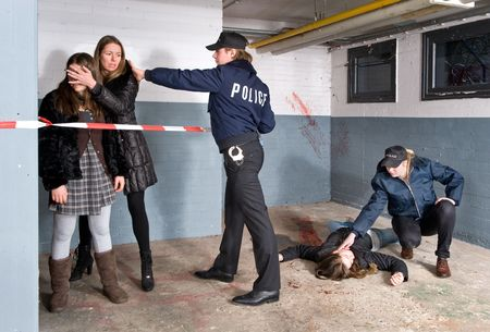 bystanders: Policeman setting the perimeter of a crime scene whilst keeping the bystanders at a distance. A mother is shielding off her young daughters vision of the horrible murder that just occured.