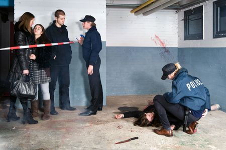 crime scene tape: Bystanders being held at a distance by a police man at a murder scene, with a police woman tending to the victim