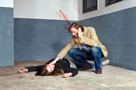 Bystander discovering a murdered woman in a basement, checking her pulse, and calling 911 on his cell phone Stock Photo - 6492785