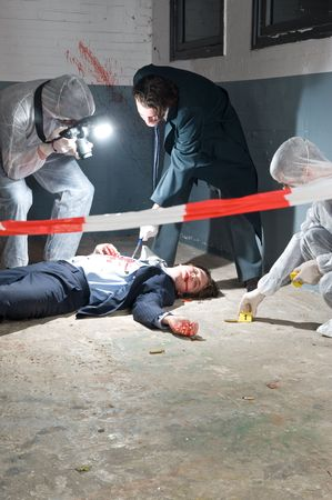 scene of a crime: Murder scene with two forensic analysts and a police lieutenant investigating a crime on a businessman in a basement Stock Photo