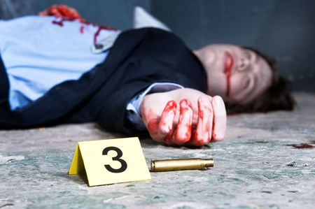 gruesome: Empty cartridge found on a crime scene with a yellow placard with number three and a dead body in the background  Stock Photo