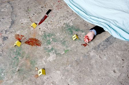 A covered corpse, with a bloody hand sticking out from underneath the shroud, surrounded by evidence: the murder weapon, a bloody foot print, and a cigarette butt photo