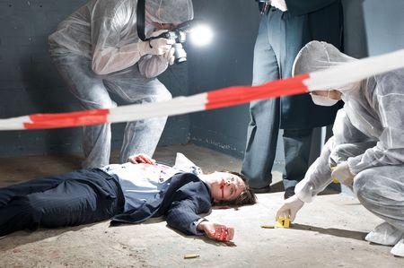 vermoord: Moordscène met twee forensische analisten en een luitenant van de politie onderzoekt een misdaad op een zaken man in een scène basementMurder met twee forensische analisten en een luitenant van de politie onderzoekt een misdaad op een zaken man in een kelder  Stockfoto
