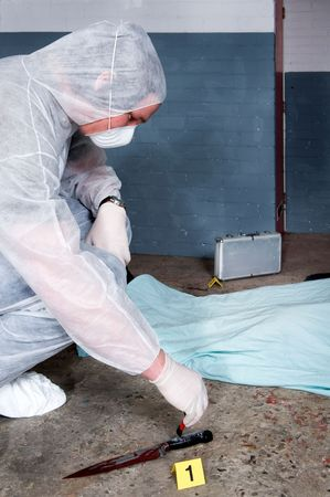 dusting: Forensic expert dusting for fingerprints on knife - the murder weapon at a gruesome crime scene Stock Photo