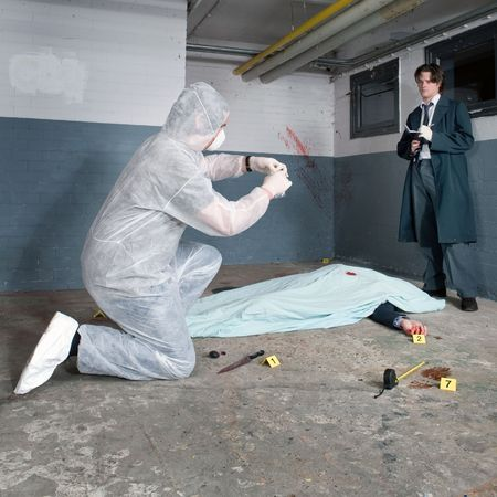 Forensic expert bagging evidence at a crime scene whilst a police inspector is taking notes around the corpse of a murdered businessman Stock Photo