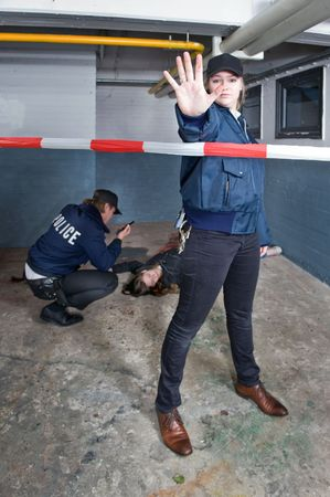 Policewoman making a stopping gesture with a blood stained outstretched hand to keep a bystander away from the perimeter of a crime scene photo
