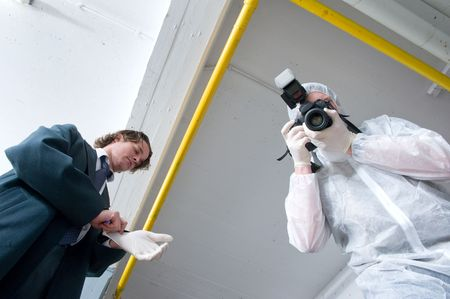 scene of the crime: Two policemen hovering over a dead body. A police lieutenant putting on his rubber gloves, and a forensics experts taking pictures of the deceased. Stock Photo