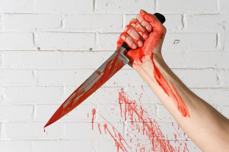 Blood covered knife, still dripping, in the hands of a murderer, with blood spatter on the brick wall.