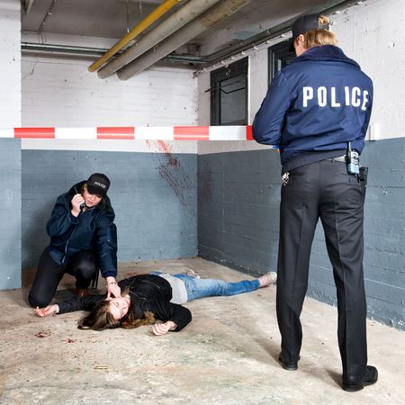 gunshot: Policeman securing the perimeter of a murder scene with cordon tape, whilst his female colleague checks the victim for vital signs Stock Photo