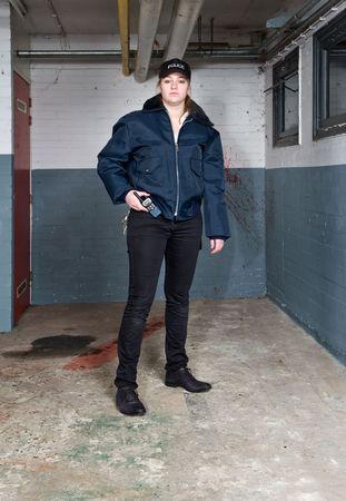 mujer policia: Policewoman mirando dura y posando en la escena de un crimen de s�tano