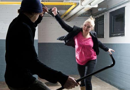 defensa personal: Mujer joven defender a s� misma con su bolso contra un criminal armado con una palanca.  Foto de archivo