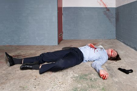 Murdered businessman lying on the floor of a basement, the gun next to the dead body photo