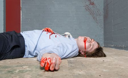 Murder victim lying on the floor, being shot in a basement, with blood splatter on the wall photo