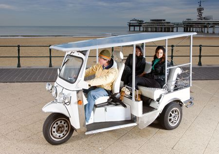Solar powered tuc tuc at the beach, picking up two young women photo