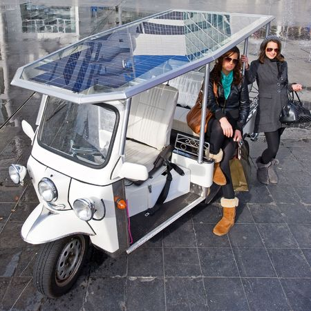 Two young women posing next to a solar powered tuc tuc in a corporate urban surrounding photo