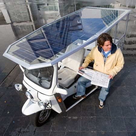 fare: Driver of a solar powered tuc tuc waiting for his next fare Stock Photo