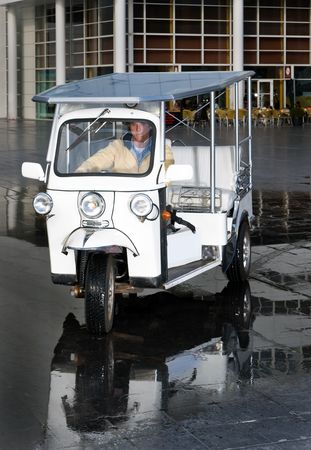 Solar powered electrical tuc tuc approaching the camera in an urban environment photo