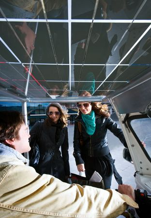 Two women discussing a fare in a solar powered tuc tuc photo