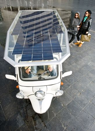 Two women looking at a solar powered tuc tuc waiting for its next fare photo