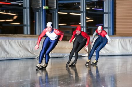 ice rink: Three speed skaters making their laps on an indoor ice rink