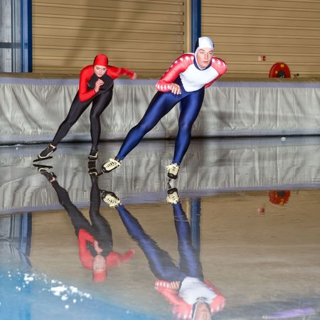 ice rink: Speed skaters during a race in an indoors ice rink Stock Photo