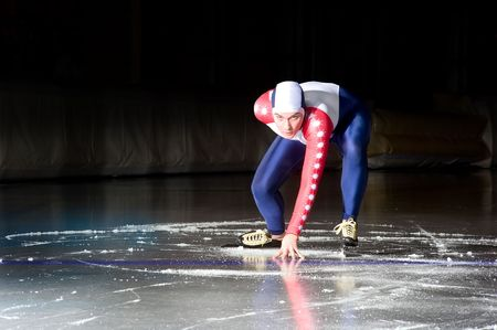 Speed skater at the starting line on an indoor ice rink