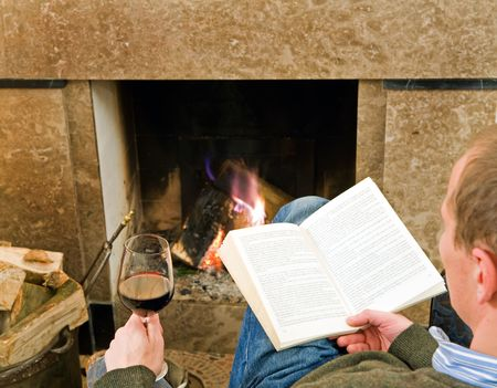 on lap: Man reading a book and drinking a glass of wine by the fireplace, relaxing.