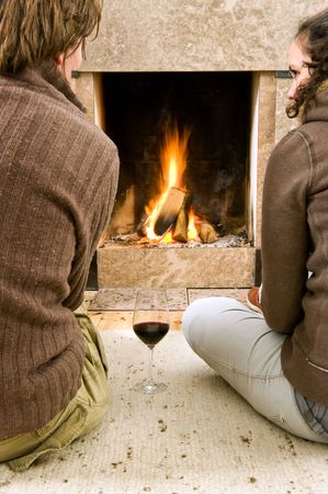 Young couple enjoying the warmth of a fire with a glass of wine photo