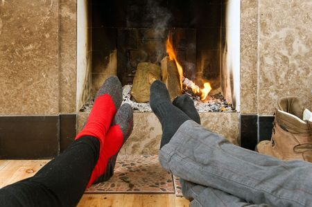 The feet of two hikers warming up by the fire after a long hike on a winters day photo