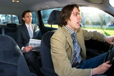 passenger vehicle: A businessman in the backseat of a taxi