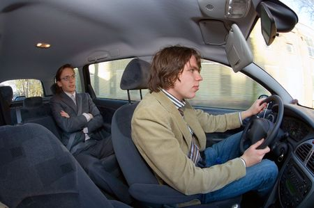 A businessman in the backseat of a taxi, driving through an urban area photo