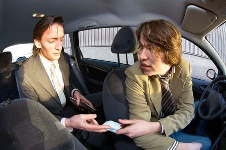 A businessman paying the fare to the taxi driver photo