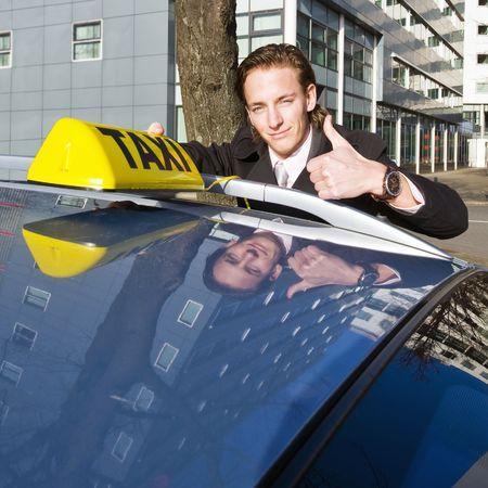 taxi: Un conductor de taxi sonriente renunciar a un pulgares mientras se coloca su taxi firmar en el techo de su coche