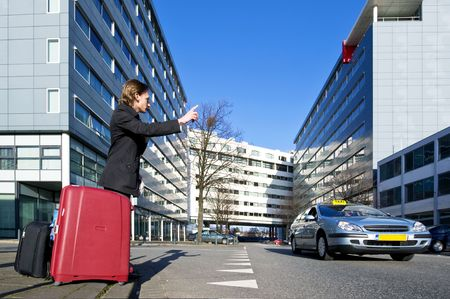 A businessman with several suitcases flagging a taxi photo