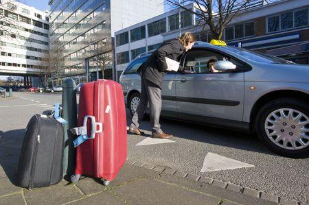taxista: Un hombre de negocios discutiendo su tarifa con un conductor de taxi Foto de archivo