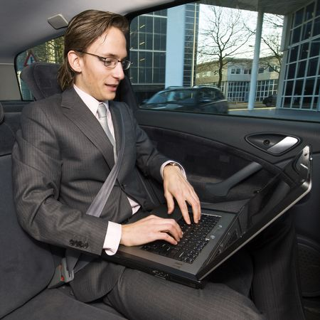 A businessman working in the backseat of a taxi being driven through a financial district photo