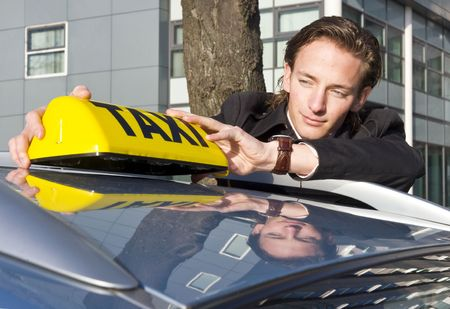 a yellow taxi: A cab driver proudly placing his taxi sign on the roof of his car
