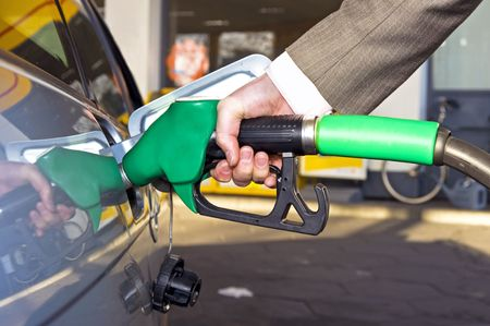 gas nozzle: A mans hand filling up a car with gas or petrol at a gas station.  Stock Photo