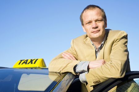 taxis: A taxi driver posing behind the front door of his cab Stock Photo